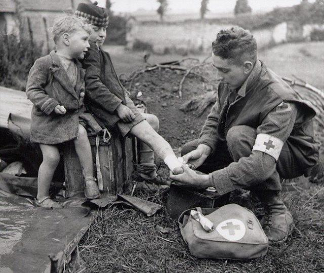 Um médico enfaixa o pé machucado de uma criança (Segunda Guerra Mundial, 1944)
