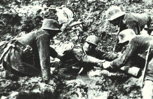Três soldados alemães ajudam um francês preso na lama (Primeira Guerra Mundial, 1916)