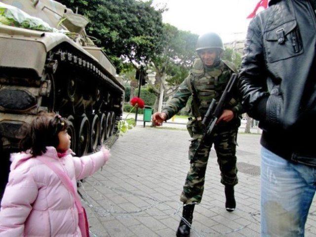"""Uma menina tunisina entrega uma rosa para um soldado depois que o exército recusou-se a atirar contra os manifestantes e declarou que iria """"defender a revolução"""" (Revolução na Tunísia, 2011)"""