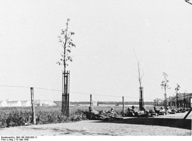 As tropas alemãs tomam uma parte da estrada ao lado do rio de Maas. No fundo uma ponte destruída pode ser vista. Foi demolido pelo exército holandês para negar seu uso aos alemães. - Fatos Militares