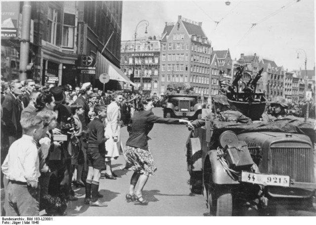 As tropas alemãs vitoriosas entram em Amsterdam. A maioria do publico olha em silêncio, e alguns cumprimentam os ocupantes. - Fatos Militares