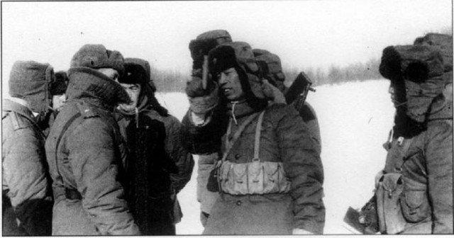 """Guarda de fronteira chinesa (à direita) acenando o """"Livro Vermelho"""" de Mao na frente de um guarda fronteiriço soviético"""