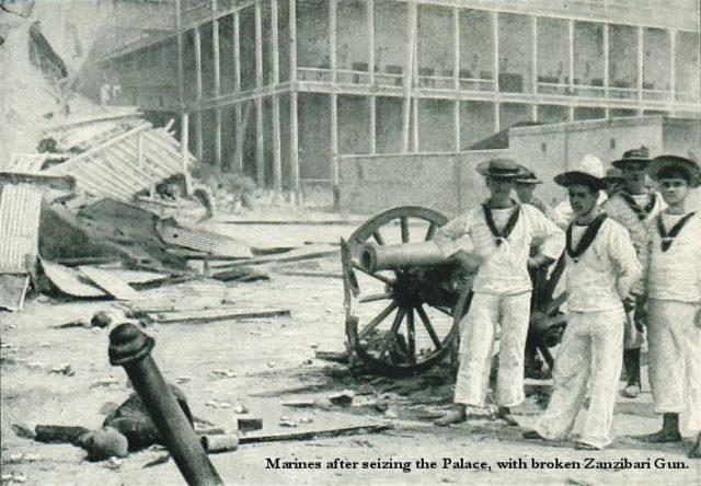 Os marinheiros britânicos posam com um canhão capturado fora do palácio do sultão após a Guerra Anglo-Zanzibar.