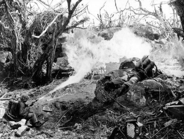 Marines lançando fogo contra uma posição japonesa em Iwo Jima