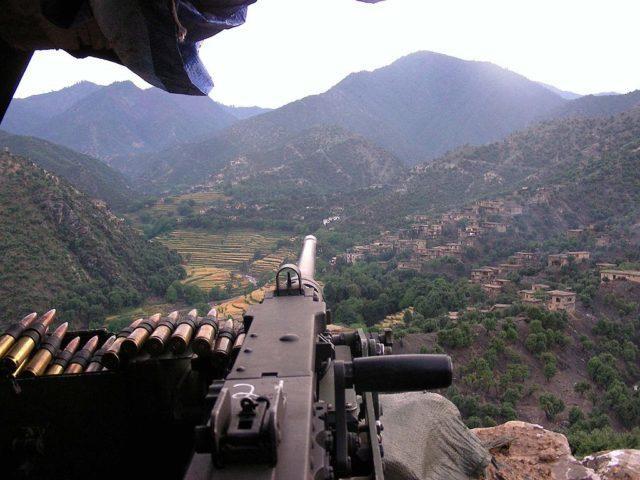 Soldado vigia vale Korengal no Afeganistão, com sua metralhadora pesada M2HB