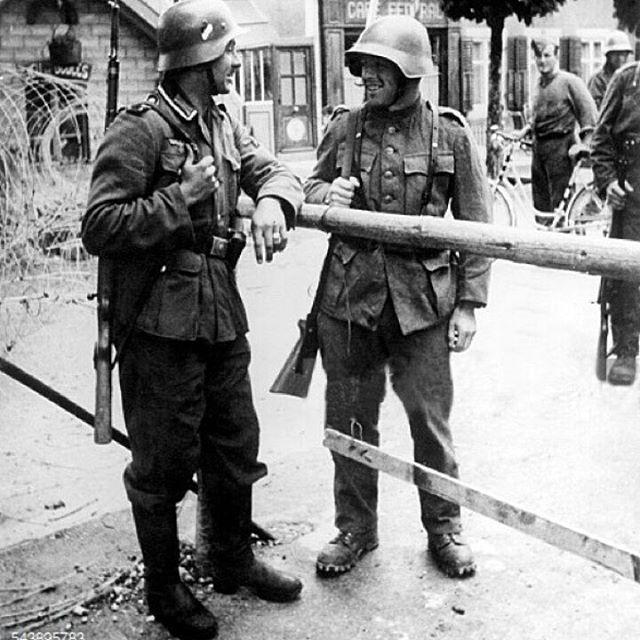 Soldado alemão e soldado suíço conversando na fronteira.