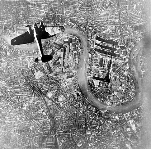 Um avião bombardeiro alemão Heinkel He 111 sobrevoando uma cidade da Inglaterra.
