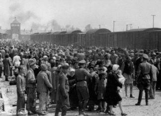 Guardas nazistas cercam prisioneiros que chegam na rampa de descarga do campo de concentração de Auschwitz, por volta de maio junho de 1944.